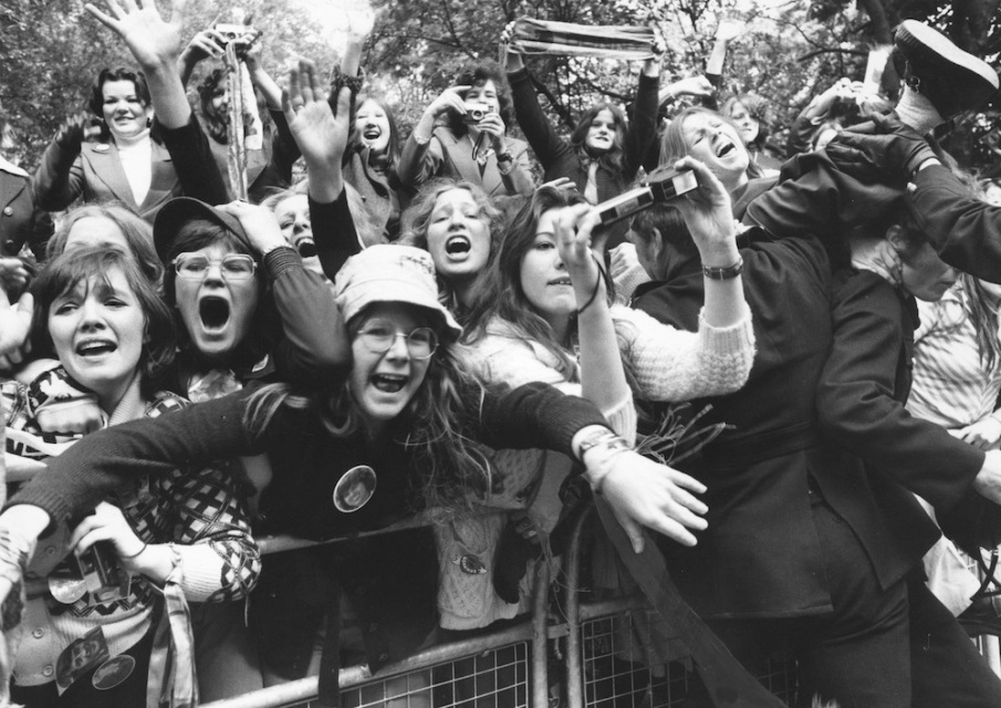 27th May 1975:  A crowd of excited fans of the American pop group The Osmonds wait behind a barrier in Eaton Square where the group is staying during a visit to London, hoping for a glimpse of the family.  (Photo by Central Press/Getty Images)